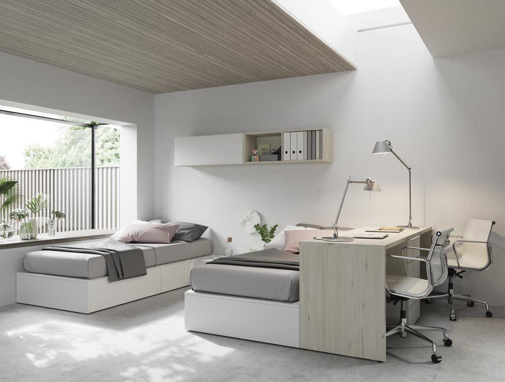 Habitación juvenil con zona dormitorio con dos camas y zona estudio con mesa y cajones