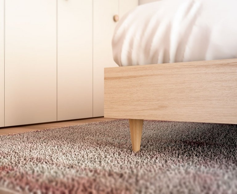 Detalle de la pata madera que tiene la cama